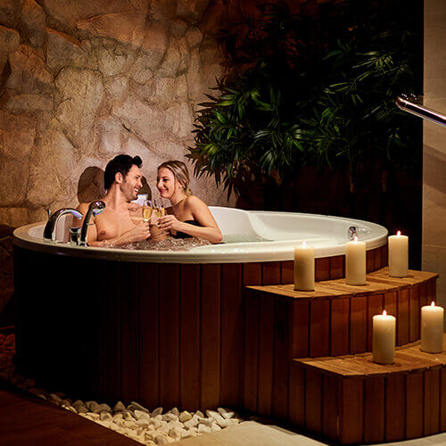 Couple in a hot spa having a drink